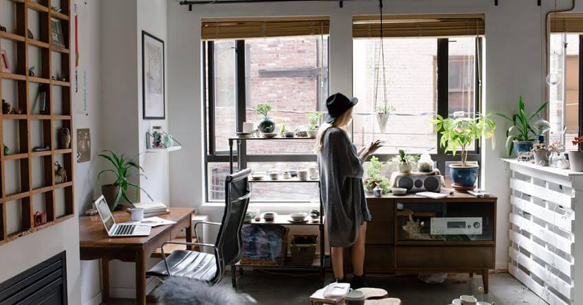 Devojka stoji pored prozora