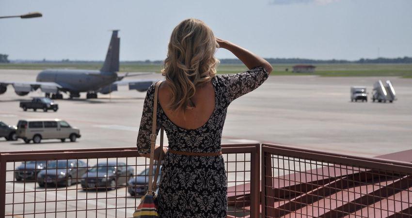 Žena gleda na pistu sa avionima